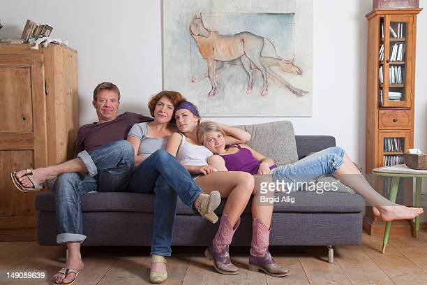 Family in four relaxing on sofa