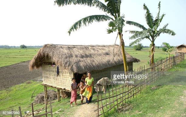 Family in front of bamboo cottages at majuli island, Assam, India