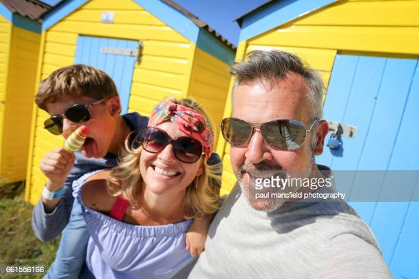 Family in front of colourful beach huts