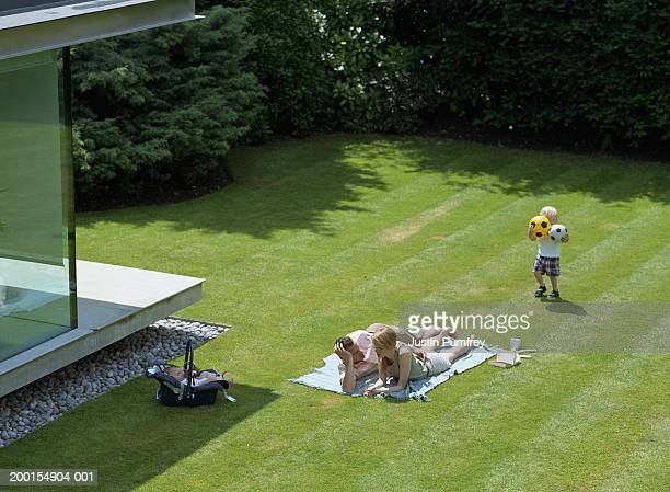family in garden, parents lying on blanket, elevated view - lying on front stock pictures, royalty-free photos & images