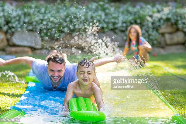 Family in garden playing water games