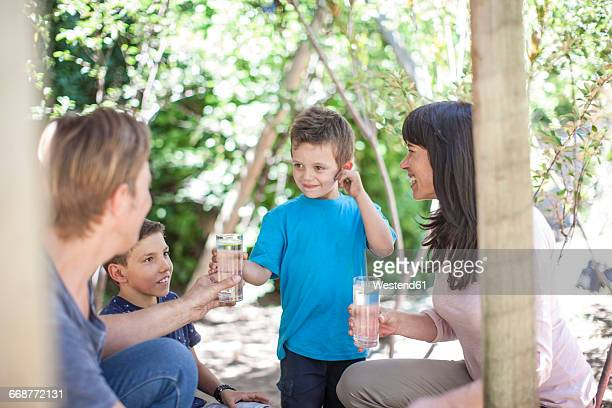 Family in garden with glasses of water