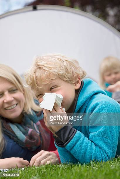 Family in garden young boy with hayfever tissue
