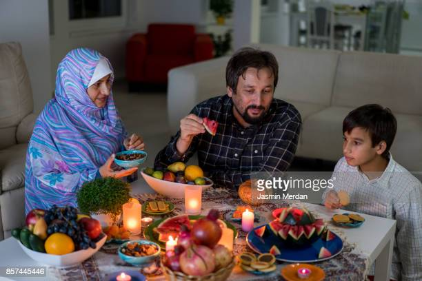 family in home talking together and eating food - イラン文化 ストックフォトと画像