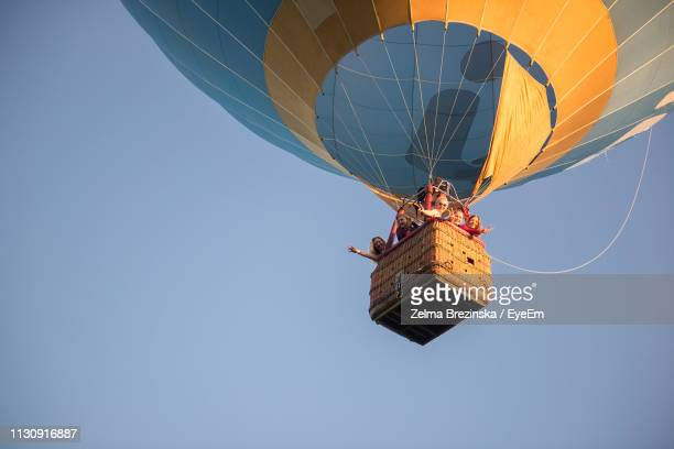 family in hot air balloon against clear sky - hot air balloon stock pictures, royalty-free photos & images