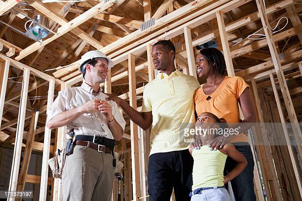 Family in house under construction with builder