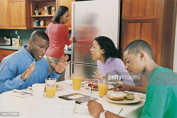 Family in Kitchen at Breakfast With Father and Daughter Arguing