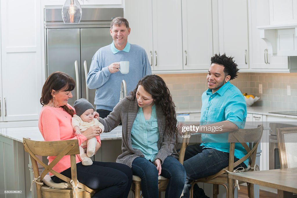 Family in kitchen, grandmother holding baby : Stock Photo