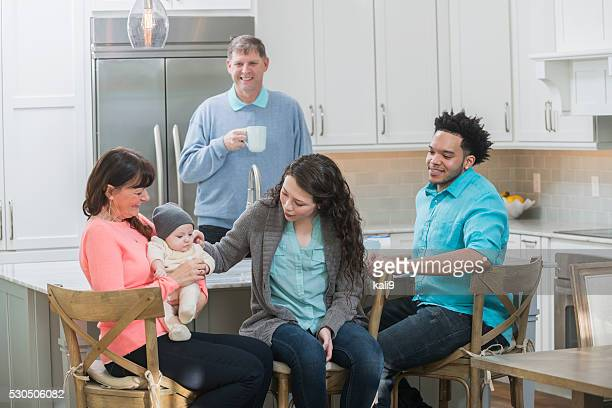 Family in kitchen, grandmother holding baby