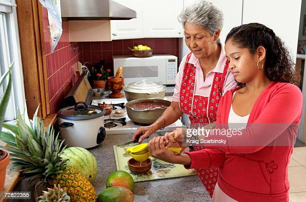 Family in kitchen, grandmother watching granddaughter (10-12) squeezing lime