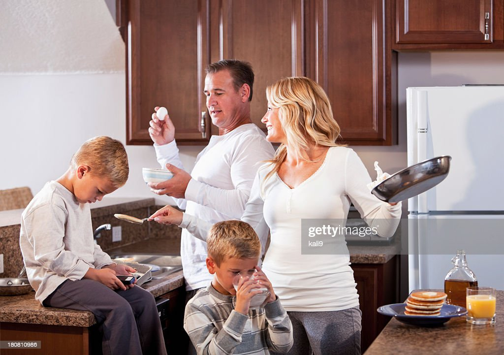 Family in kitchen making breakfast : Stock Photo