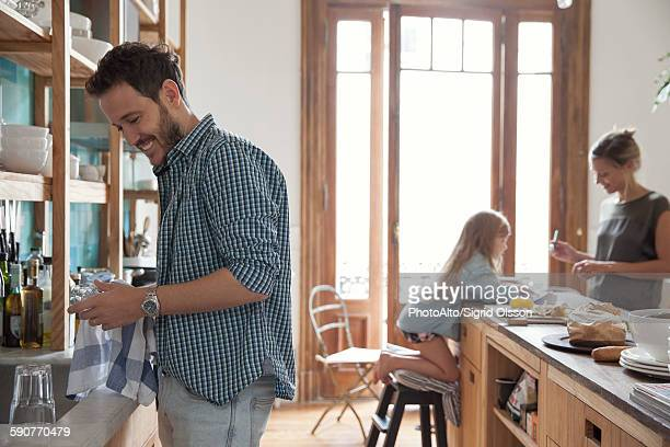 Family in kitchen, man drying dishes in foreground
