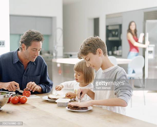 Family in kitchen (focus on father and children (4-12) at table)
