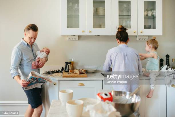 family in kitchen - morgen stockfoto's en -beelden