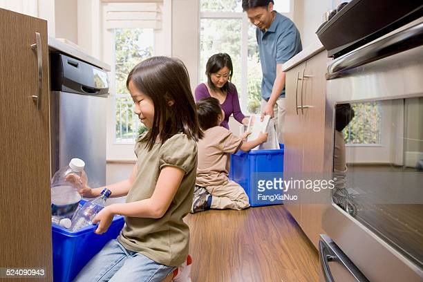 family in kitchen recycling paper and plastic - responsibility stock pictures, royalty-free photos & images