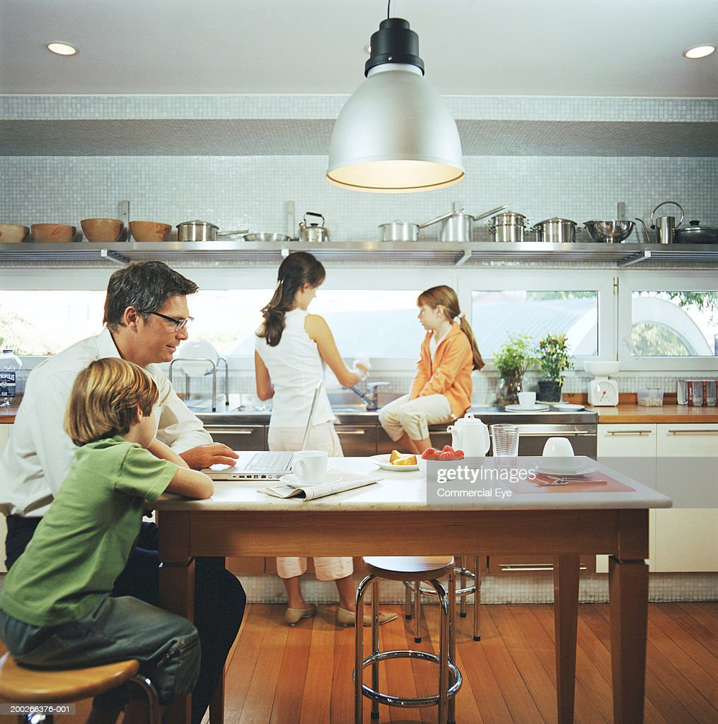 Family in kitchen, side view : Stock Photo