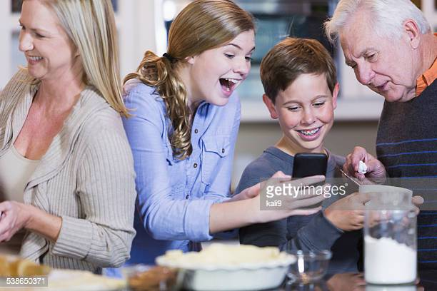 Family in kitchen, teen with mobile phone