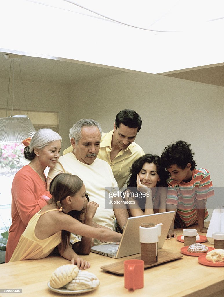 Family in kitchen with laptop computer : Stock Photo