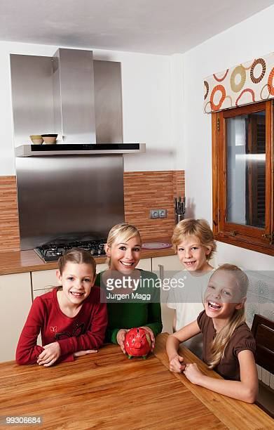Family in kitchen with piggy bank