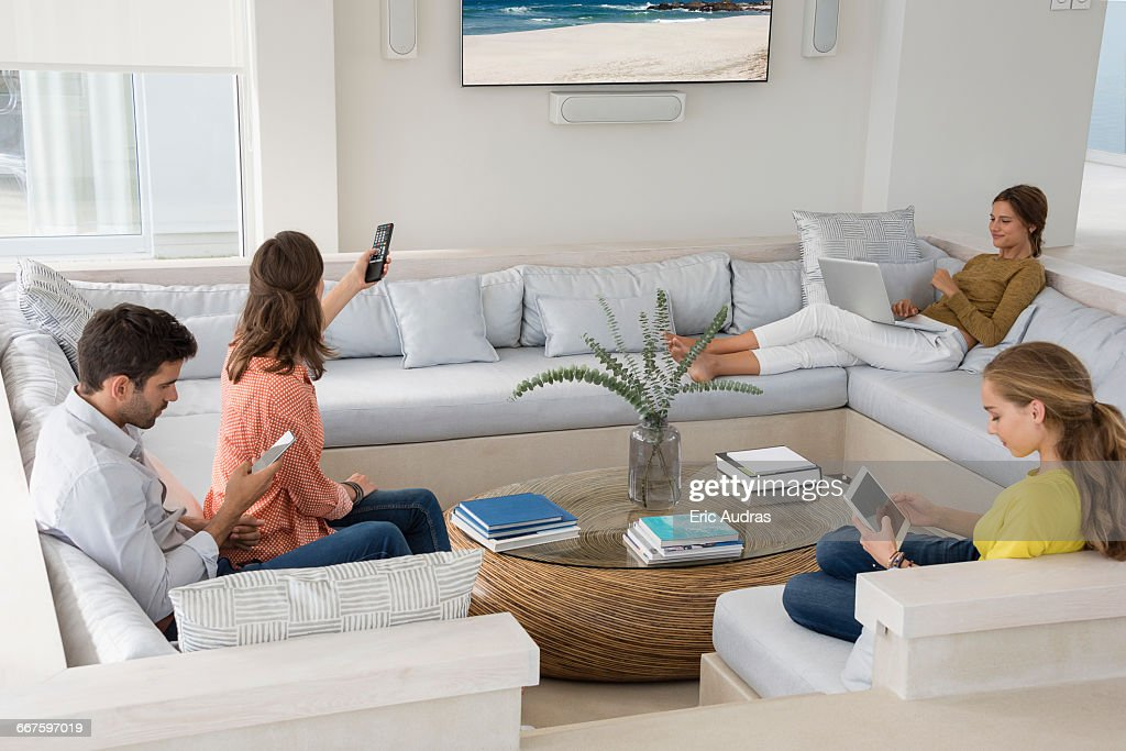 family in living room busy in different activities stock