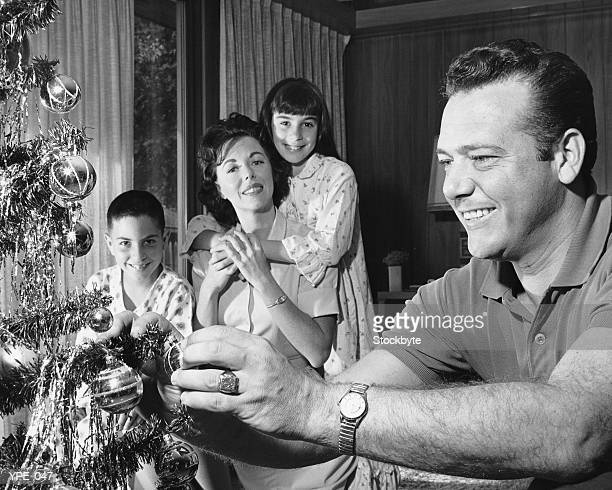 Family in living room, father decorating Christmas tree