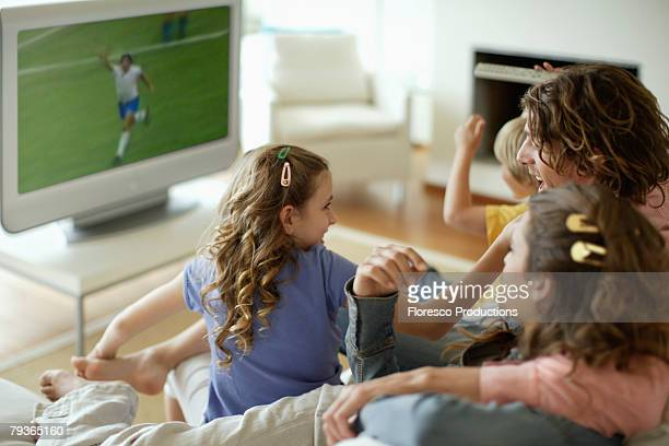 family in living room watching sports on television - family watching tv stock pictures, royalty-free photos & images