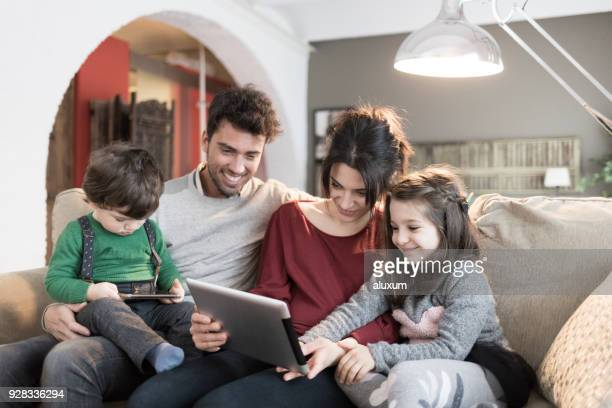 Family in livingroom looking at tablet and smartphone devices