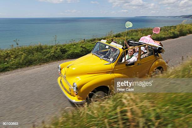 family in open top car on coastal road