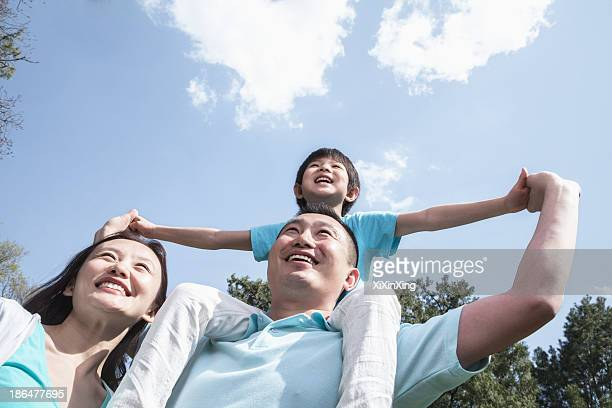 Family in park with son on father's shoulders.