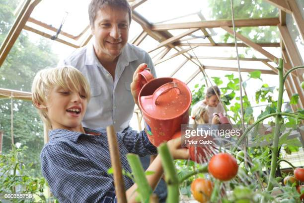Family in poly tunnel watering plants