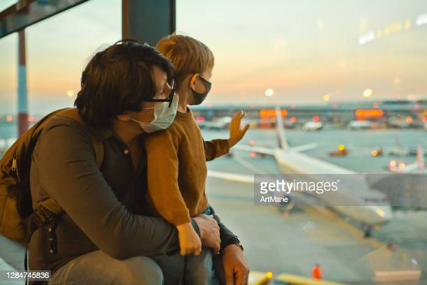family in protective face masks in airport during covid-19 pandemic - airport stock pictures, royalty-free photos & images
