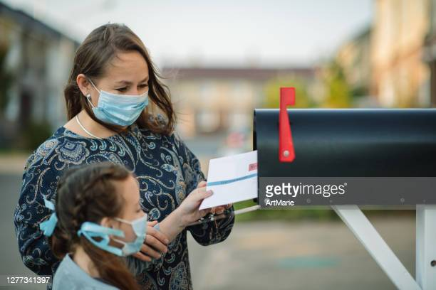 family in protective face masks sending or receiving mail with mailbox near house - voting by mail stock pictures, royalty-free photos & images
