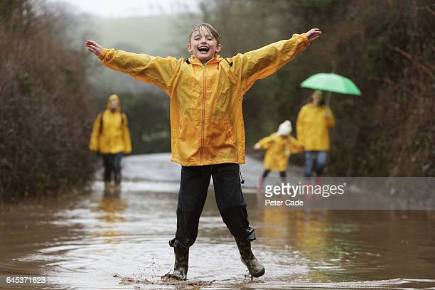 family in rain, boy jumping in puddle - mother son shower stock photos and pictures