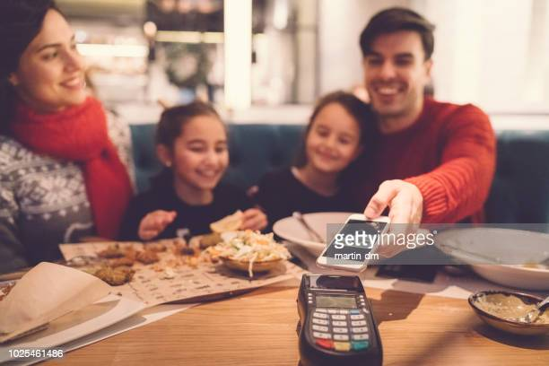 family in restaurant paying contactless - nfc stock pictures, royalty-free photos & images