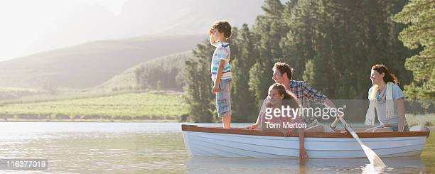 family in rowboat on lake - recreational boat stock pictures, royalty-free photos & images