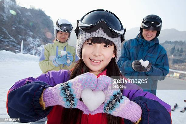 family in ski resort, daughter showing snow heart - mitten stock pictures, royalty-free photos & images