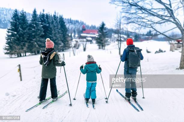 family in snowy winter landscape on cross-country-ski - nordic skiing event stock pictures, royalty-free photos & images