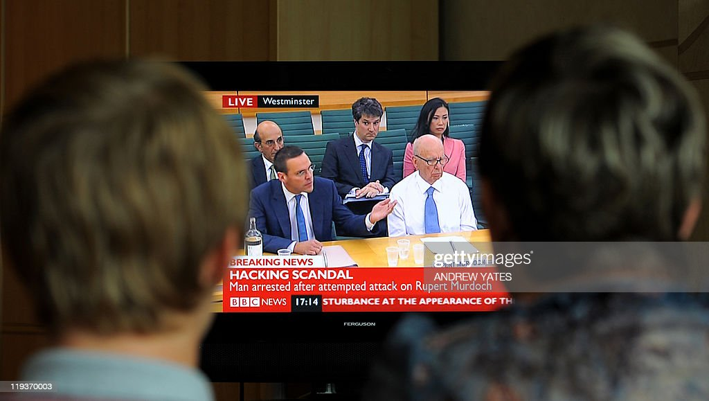 A family in Stockport, northern England, on July 19 2011, watch a television showing News Corporation Chief Rupert Murdoch and his son James after a man allegedly threw a white substance at Rupert Murdoch during their evidence to a Parliamentary Select Committee on the phone hacking scandal. Media mogul Rupert Murdoch was hit with a plate of white foam while testifying to a British parliamentary committee and a man was arrested, an AFP reporter said.