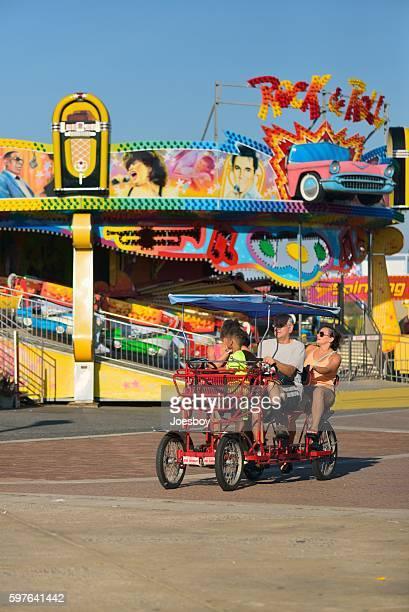 family in surrey bike on ocean city boardwalk - ocean city maryland stock pictures, royalty-free photos & images