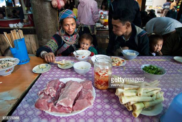 Family in the Food market stand serving food Sapa region North Vietnam Asia Ethnic Hmong tribe shopping at Muong Hum market Vietnam