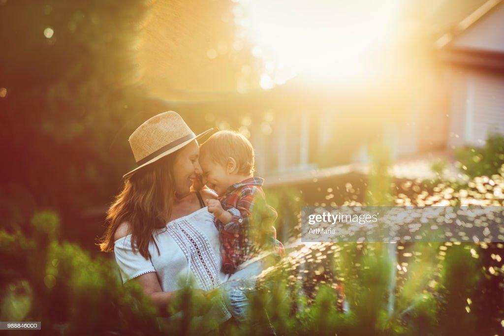 Family in the garden in sunset : Stock Photo
