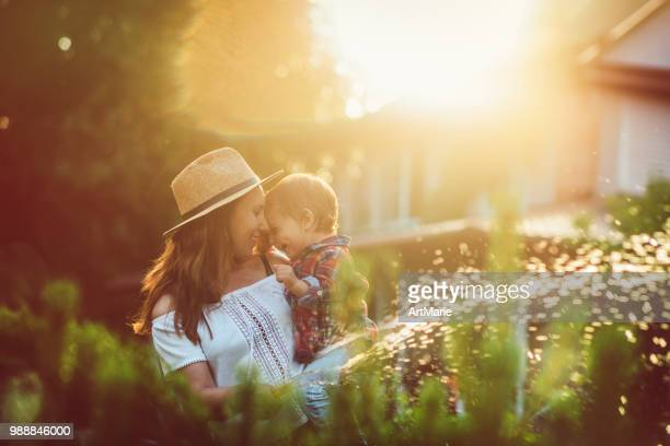 family in the garden in sunset - flowerbed stock pictures, royalty-free photos & images