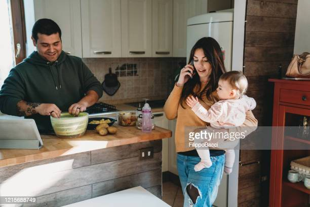 family in the kitchen - mum is making a call while dad is cooking - lockdown stock pictures, royalty-free photos & images