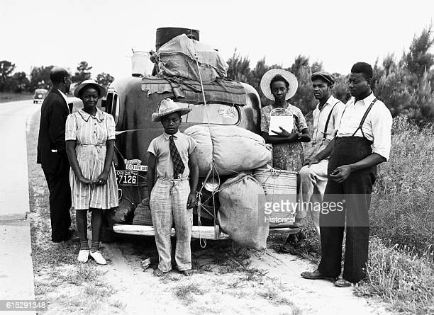 A family in the midst of a move rest alongside a country road beside their heavily laden car