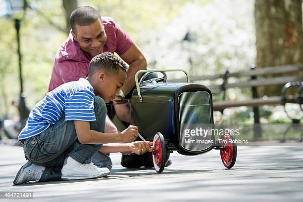 A family in the park on a sunny day. A boy repairing an old fashioned toy peddle car.