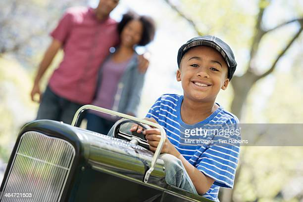 A family in the park on a sunny day. A boy riding an old fashioned toy peddle car.