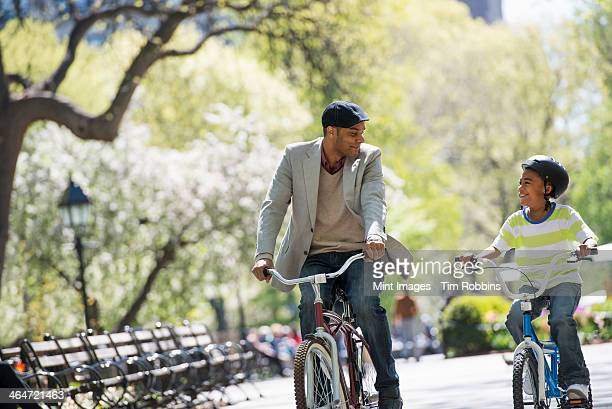 a family in the park on a sunny day. bicycling and having fun. a father and son side by side. - human relationship stock pictures, royalty-free photos & images