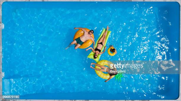 family in the pool - inflatable ring stock pictures, royalty-free photos & images