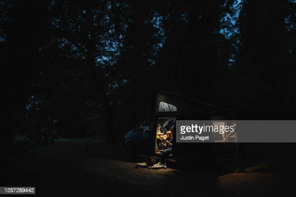 family in their campervan in the forest at dusk - wireless technology stock pictures, royalty-free photos & images