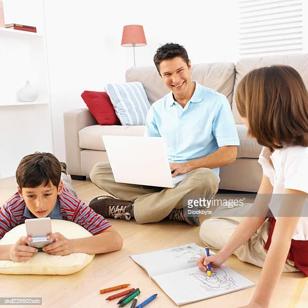 family in their living room - ligga på mage bildbanksfoton och bilder